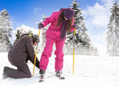 Man helps her girlfriend to put her skis — Stock Photo