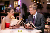 Happy couple with menu card — Stock Photo