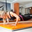Young woman looking down while doing push-ups — Stock Photo #39628859