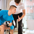 Mdoing weights lifting with trainer — Stock Photo #39622205