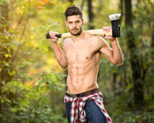 Sexy lumberjack in forest — Stock Photo
