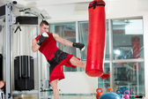 Man practicing some kicks with a punching bag — Stock Photo