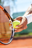 Hand with tennis ball and racket — Stock Photo