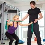 Постер, плакат: Woman exercising with personal trainer