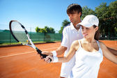 Woman and male tennis instructor practicing — Stock Photo