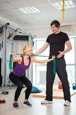 Vrouw uitoefenend met persoonlijke trainer — Stockfoto