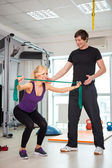Woman exercising with personal trainer — Stock Photo