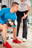 Man exercising under supervision trainer — Stock Photo