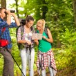Group of hikers with map and binoculars — Stock Photo