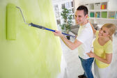 Couple painting wall with paint roller — ストック写真
