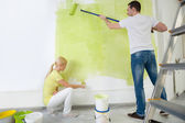 Young couple painting wall — Stok fotoğraf