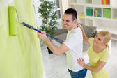 Smiling couple painting hew home  — ストック写真