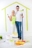 Happy couple painting their new home — Stock Photo