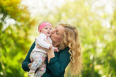 Mom kissing her daughter baby — Stock Photo