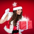 Santa girl adding little magic to Christmas present — Stock Photo #4458364