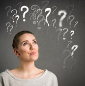 Young woman thinking with question marks over head  — Stock Photo