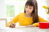 Adorable girl writing  greeting card — Stock Photo