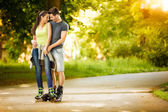 Love couple ride rollerblades in the park — Stock Photo