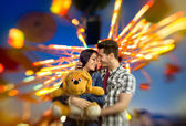 Love couple with colorful carousel in background — Stock Photo