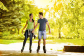 Young couple roller-skating in the park — Stock Photo