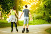 Couple ride rollerblades in the park — Stock Photo