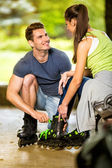 Young couple preparing for rollerblades — Stock Photo