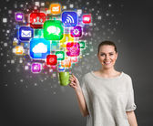 Beautiful girl holding coffee cup with colorful media icons — Stock Photo
