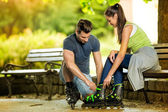 Man helping his girlfriends to put rollerblades — Stock Photo