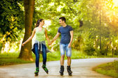 Smiling couple riding rollerblades — Foto de Stock