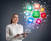 Young woman with tablet and colorful media icons — Stock Photo
