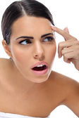 Surprised woman looking problem on her skin — Stockfoto