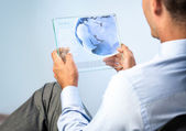 Young man with transparent futuristic tablet — Stock Photo