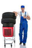 Mechanic with tires giving a thumbs up — Stock Photo