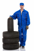 Young car mechanic with tires for the car — Foto de Stock