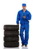 Young car mechanic with pile car tires — Foto de Stock