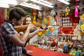 Young fun couple playing shooting games — Stock Photo