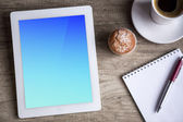 Ipad Tablet with cup of coffee over wooden table — Stock Photo