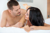 Smiling couple in bedroom — Stock Photo
