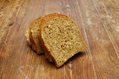 Dark wheat bread on old wooden plank — Stock Photo