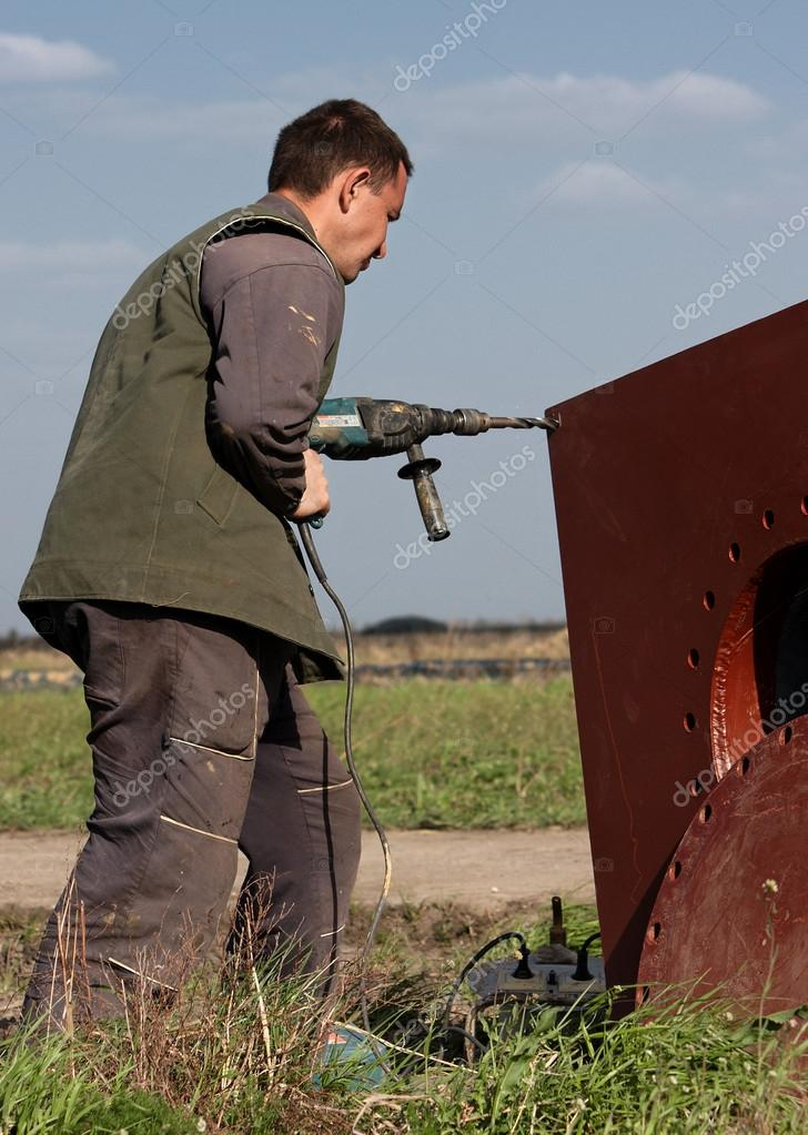 A man drilling a hole in a plate of metal, focus on man — Stock Photo #12097285