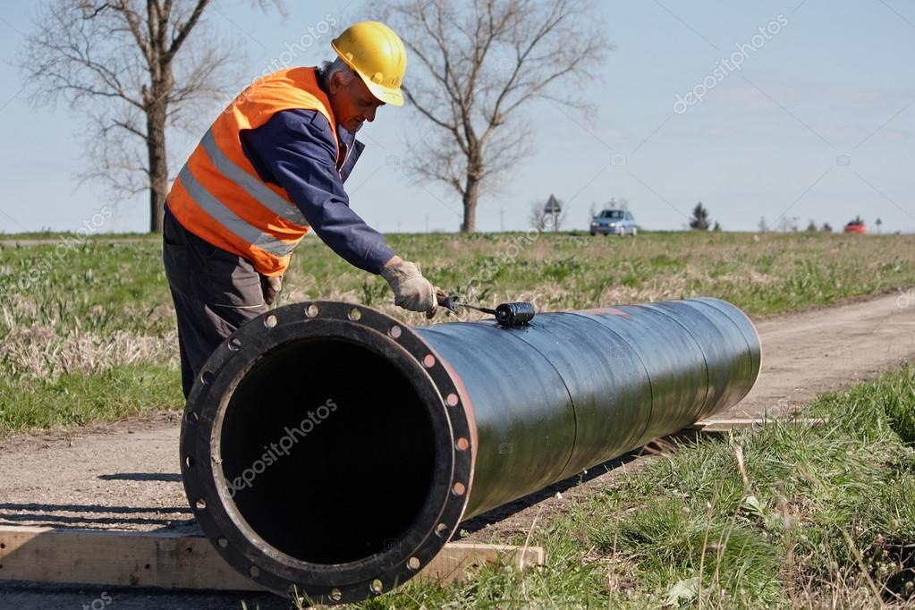 Man with roller painting a metal tube  Stock Photo #12097443