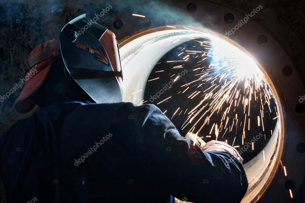 A metalworker welding a metal barrel  Stock Photo #12140296