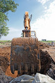 Excavator digs a hole — Stok fotoğraf