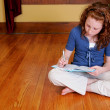 Young girl sitting on the floor writing — Stock Photo #2175746