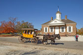 A horse-drawn carriage rides in front of the courthouse building — Stock Photo