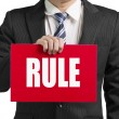 "Businessman use one hand to hold a red board with word ""RULE"" cl — Foto de Stock"