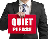 "Businessman use one hand to hold a red board with words ""QUIET P — Stock Photo"