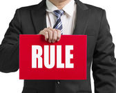 """Businessman use one hand to hold a red board with word """"RULE"""" cl — Stock Photo"""
