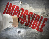 Punching, break concrete wall with word impossible on it, make i — Stock Photo
