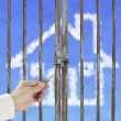 Hand hold key unlocking locked door with cloud house in blue sky — Stockfoto